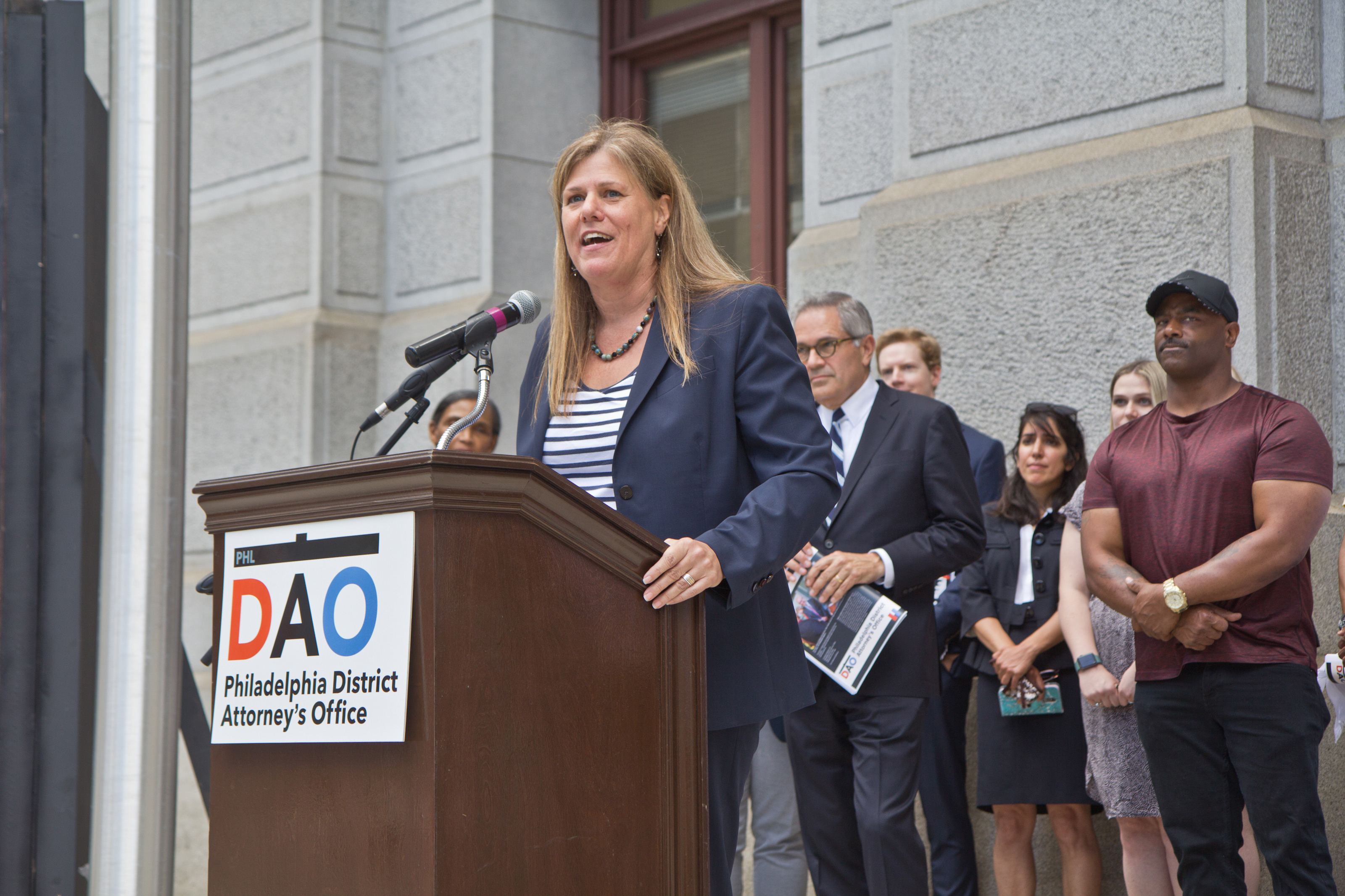 A white woman speaks at a podium, which has a sign attached reading