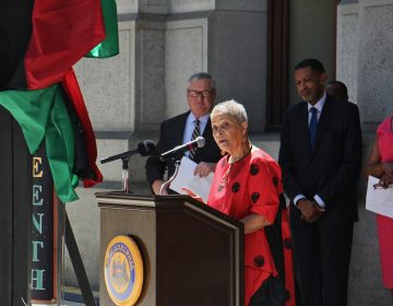 Helen Salahuddin speaks from a podium, with a Black Liberation Flag visible in the background