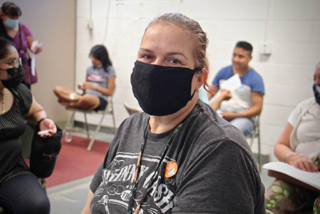 Samantha Madden sits while wearing a black face mask