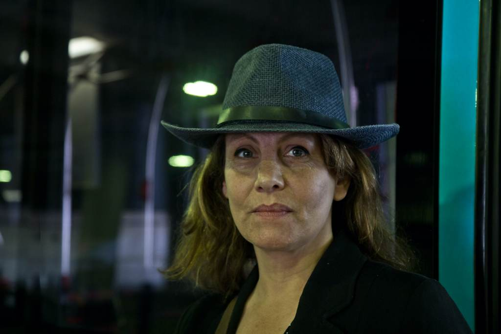 Isabelle Rigollaud wears a hat inside a transportation center