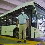 Jeffery Gallman wears a face mask in front of a KRAPF bus
