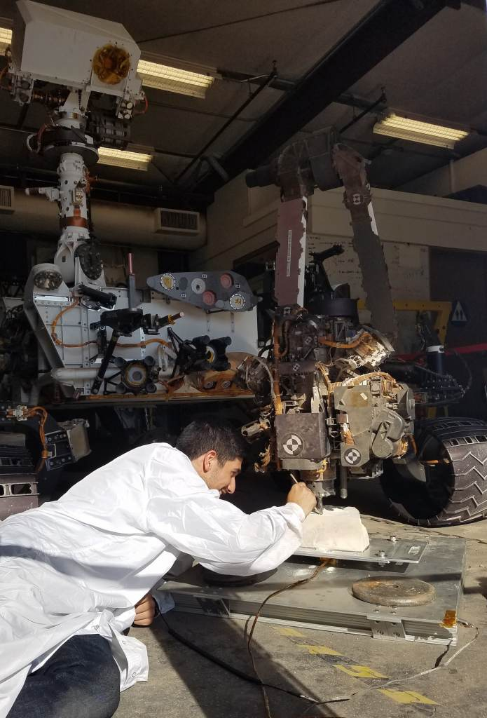 NASA robotics engineer Vladimir Arutyunov tests a new way for the Mars rover Curiosity to drill, using a clone of the rover on Earth. Photo courtesy of NASA/JPL-Caltech.