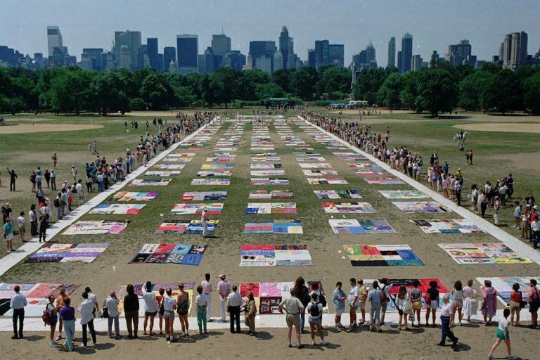 Onlookers watch as almost 1,500 quilt panels bearing the names of New York area residents who have died of AIDS are unfolded on the Great Lawn