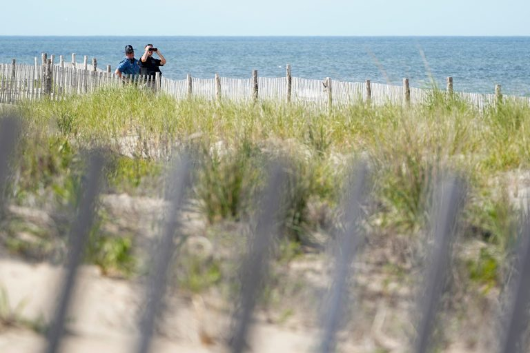Law enforcement officers guard the beach as they wait for Marine One, with President Joe Biden on board, to land at Rehoboth Beach, Del., Wednesday, June 2, 2021. Biden is spending a few days at his home in Rehoboth Beach to celebrate first lady Jill Biden's 70th birthday. (AP Photo/Susan Walsh)