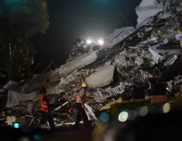 Rescue workers walk beside the rubble as rescue efforts continue