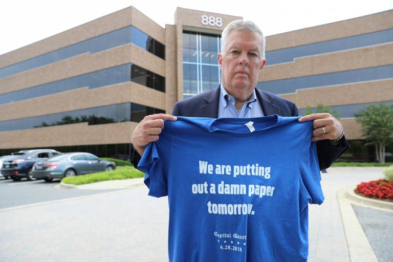 Ray Feldmann, who lives blocks away from the Capital Gazette's former office where five people were killed in a 2018 mass shooting, stands in front of the building Monday, June 21, 2021, in Annapolis, Md. He holds a shirt with a quote from Chase Cook, a staffer at the newspaper who is no longer there after taking a recent buyout, who made the comment in a tweet after the attack. Opening statements in the second phase of the gunman's trial to determine whether he is criminally responsible due to mental illness are scheduled for Tuesday, June 29. Jarrod Ramos already has pleaded guilty to all 23 counts against him. (AP Photo/Brian Witte)
