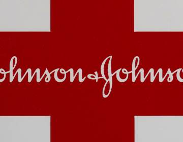 This Feb. 24, 2021 photo shows a Johnson & Johnson logo on the exterior of a first aid kit in Walpole, Mass.  The New York attorney general says Johnson & Johnson has agreed to pay $230 million to settle claims that the pharmaceutical giant helped fuel the opioid crisis. The deal requires Johnson & Johnson to make a series of payments over nine years to cover total.   (AP Photo/Steven Senne)