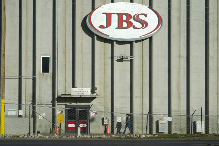 A worker walks into a JBS meat packing plant