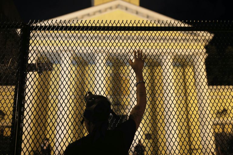 A protester calls out to police standing guard behind security fencing