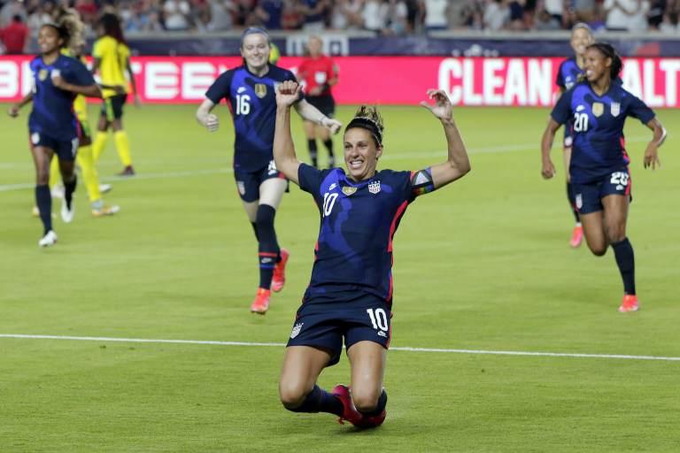 Carli Lloyd slides on astro turf during a soccer game
