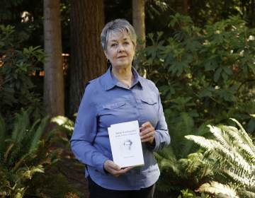 Karen McKnight stands in her backyard holding two books written by her brother