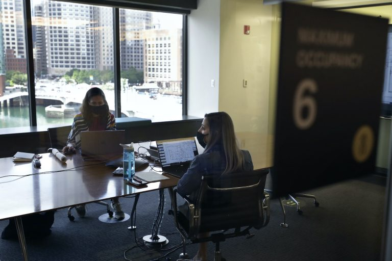 Stephanie Jones, left, and Tara Martin, right, work in a conference room while wearing face masks