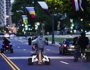 ATVs riders travel down the Benjamin Franklin Parkway