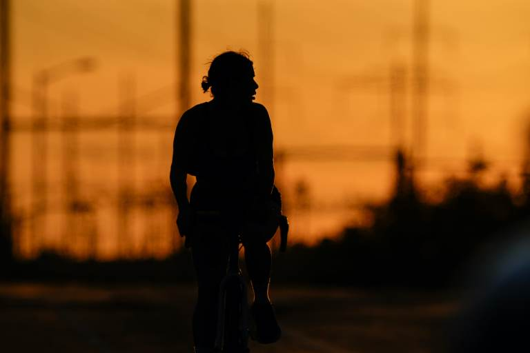 A cyclist rides in the day's diminishing light