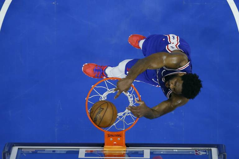 An overhead shot of Joel Embiid dunking a basketball during a playoff game