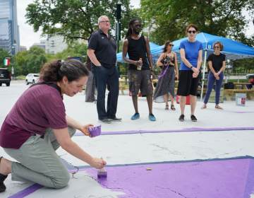 Acting Health Commissioner Dr. Cheryl Bettigole paints as Mayor Jim Kenney speaks with artist, Felix St. Fort, and Mural Arts executive director Jane Golden. (Kenny Cooper / WHYY)