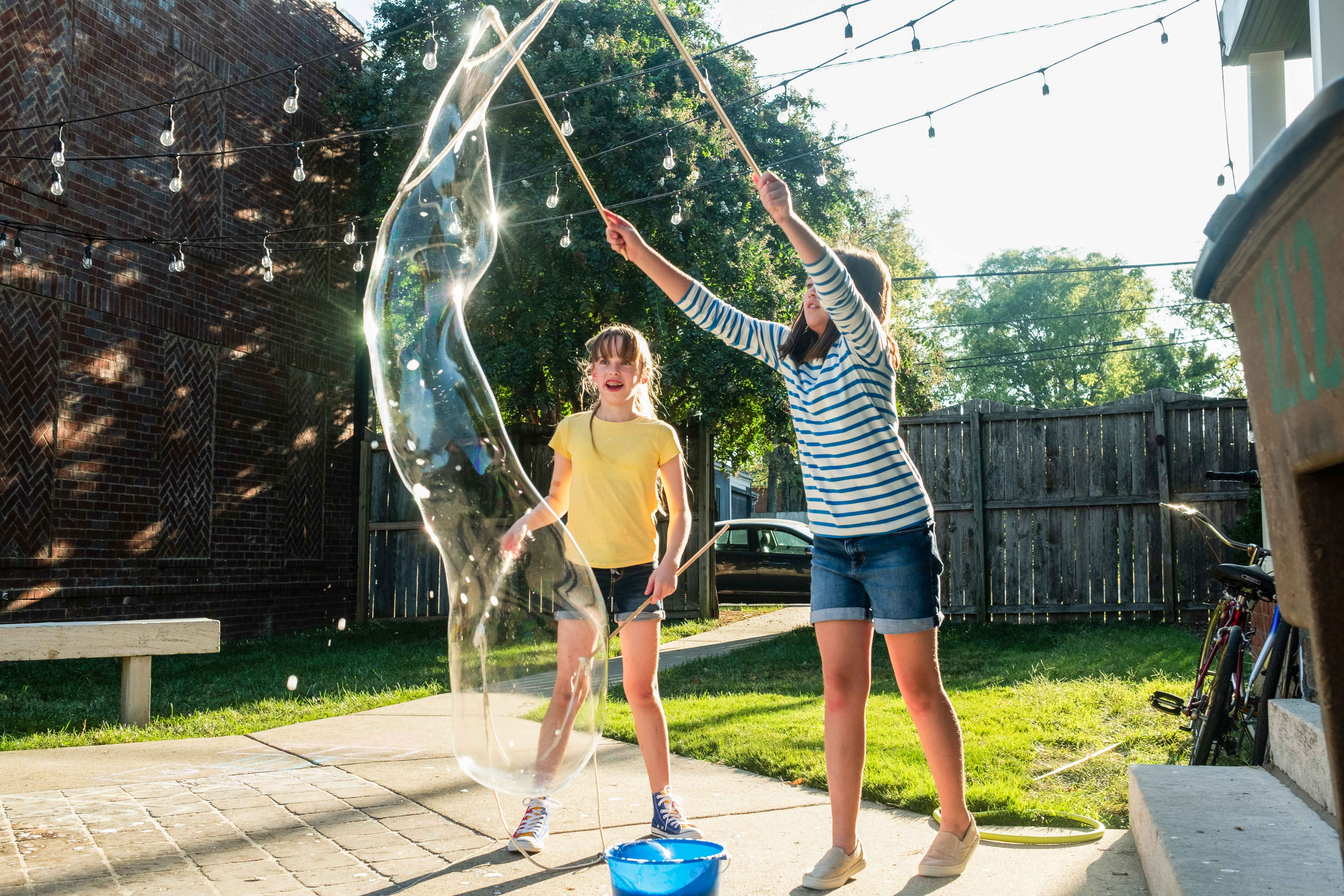 Two girls playing outside making bubbles with a soap wand