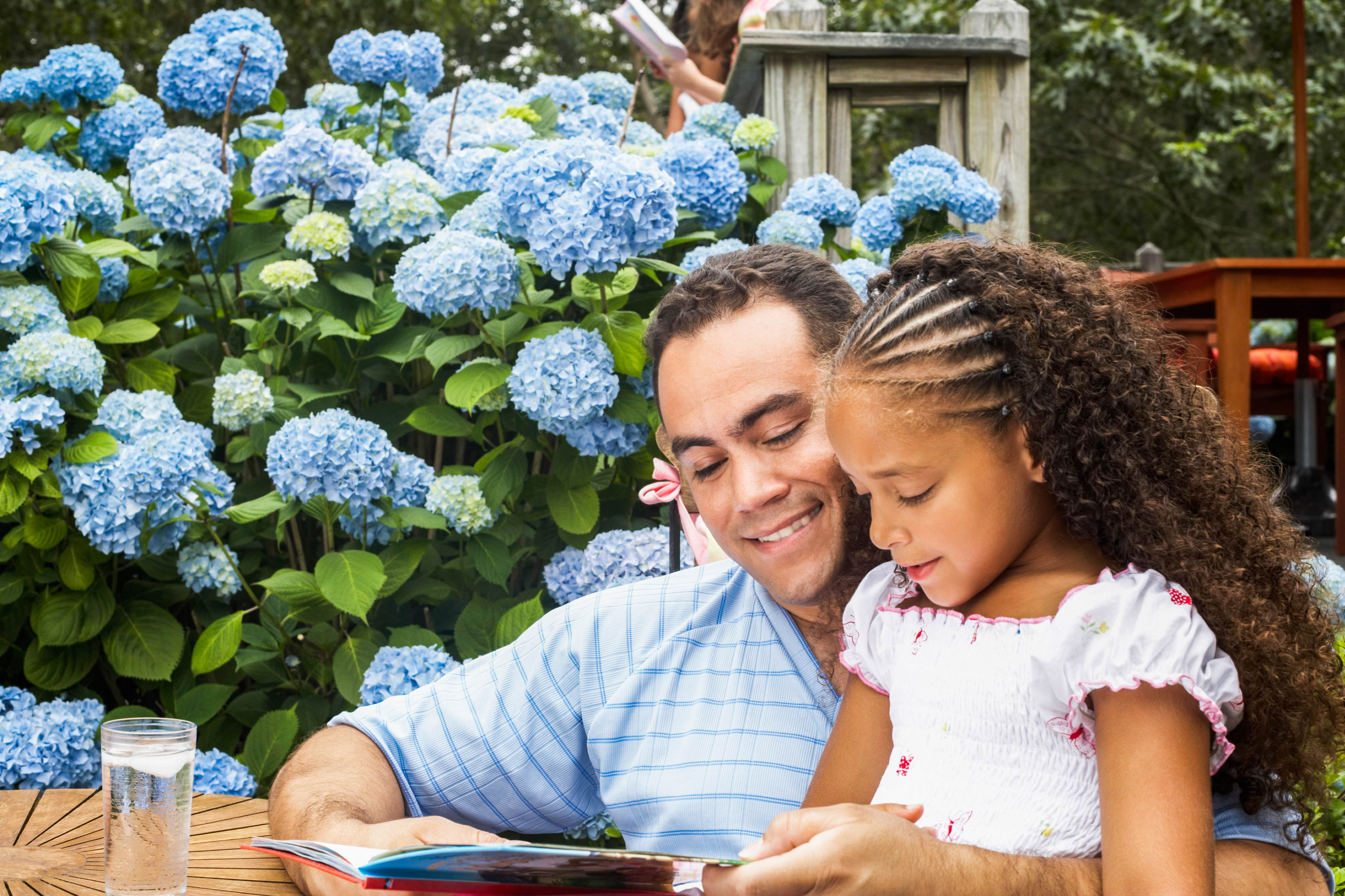 Father and daughter outside reading a book
