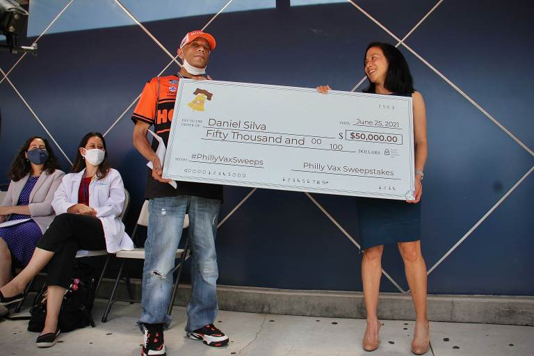 Vaccine sweepstakes winner Daniel Silva and Dr. Angela Duckworth hold a giant check during a press event at Maria de los Santos Health Center. (Emma Lee/WHYY)