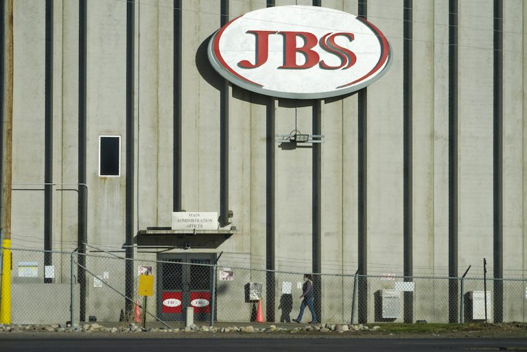 A worker heads into JBS meatpacking plant in Greeley, Colo.  A ransomware attack on the world's largest meat company is disrupting production around the world just weeks after a similar incident shut down a U.S. oil pipeline.  (AP Photo/David Zalubowski)