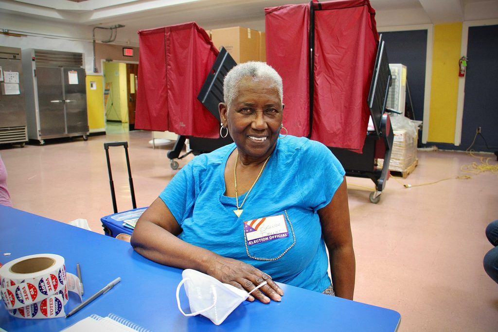 Election Official Brenda Barnes-Roman smiles while sitting at a table at a polling station