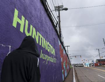 A pedestrian walks past a mural in Huntington, W.Va., Thursday, March 18, 2021. Huntington was once ground-zero for this opioid epidemic. Several years ago, they formed a team that within days visits everyone who overdoses to try to pull them back from the brink. It was a hard-fought battle, but it worked. The county's overdose rate plummeted. They wrestled down an HIV cluster. They finally felt hope. Then the pandemic arrived and it undid much of their effort: overdoses shot up again, so did HIV diagnoses. (AP Photo/David Goldman)