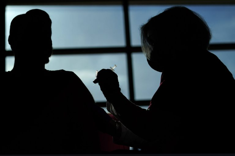 A person receives a COVID-19 vaccination from a nurse practitioner