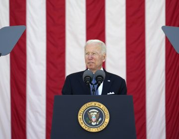 President Joe Biden speaks behind a podium, in front of an American flag