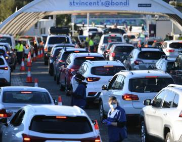 People line up in their cars to get tested for COVID-19 at a pop-up testing clinic at Bondi Beach in Sydney on Friday. Parts of Sydney will go into lockdown late Friday because of a growing coronavirus outbreak in Australia's largest city. (Dean Lewins/AP)