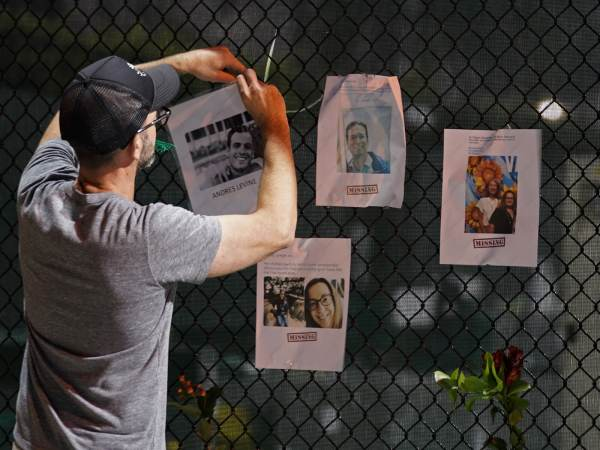 A man hangs a photo on a fence of someone missing near the site of an oceanfront condo building