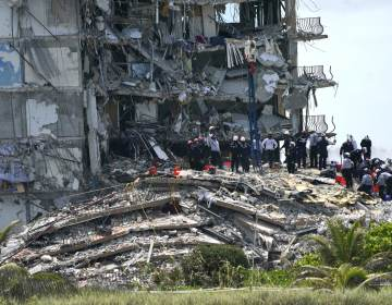 Rescue workers search in the rubble at the Champlain Towers South condominium