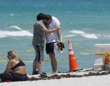 Two men console each other on the beach