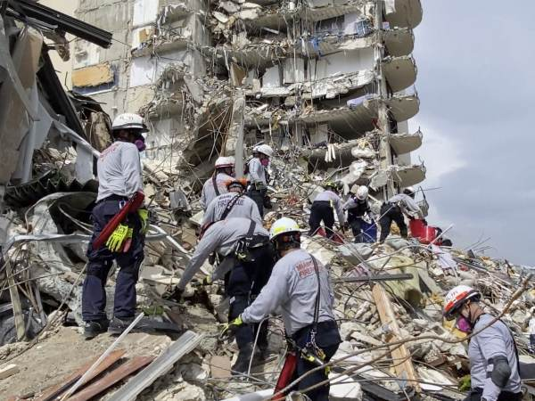 Search and rescue personnel search for survivors through the rubble at the Champlain Towers South Condo
