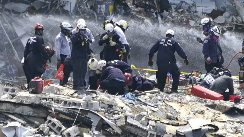 Rescue workers search the rubble of the Champlain Towers South condominium