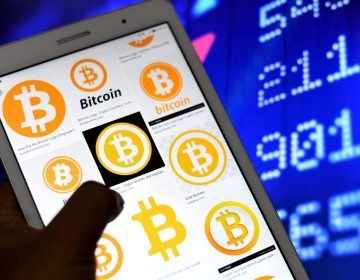 A hand holds up a phone with Bitcoin logos on it, against the backdrop of a screen with numbers on it