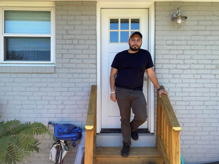 Jonathan Caballero stands on his front porch