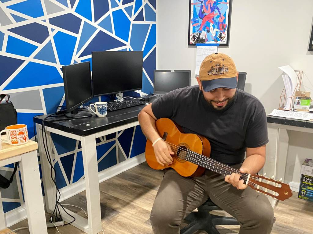 Jonathan plays the guitar while sitting at a computer desk