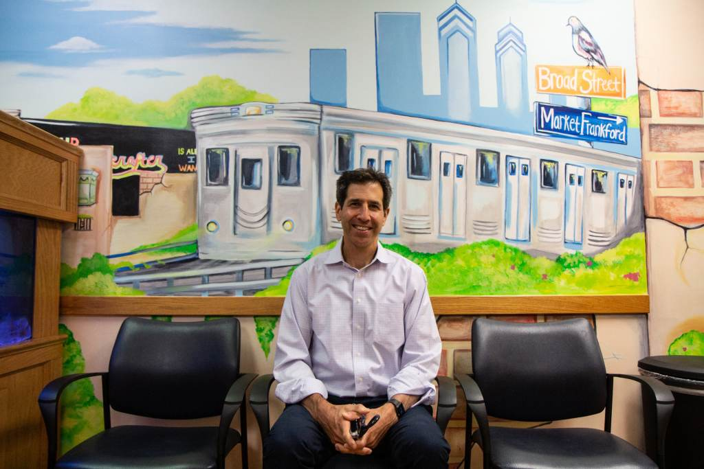 Dr. Eric Berger sits in front of an illustration of a subway in Philly