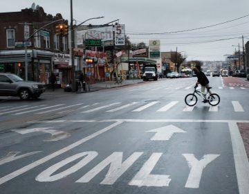 A person rides a bike across a New York street