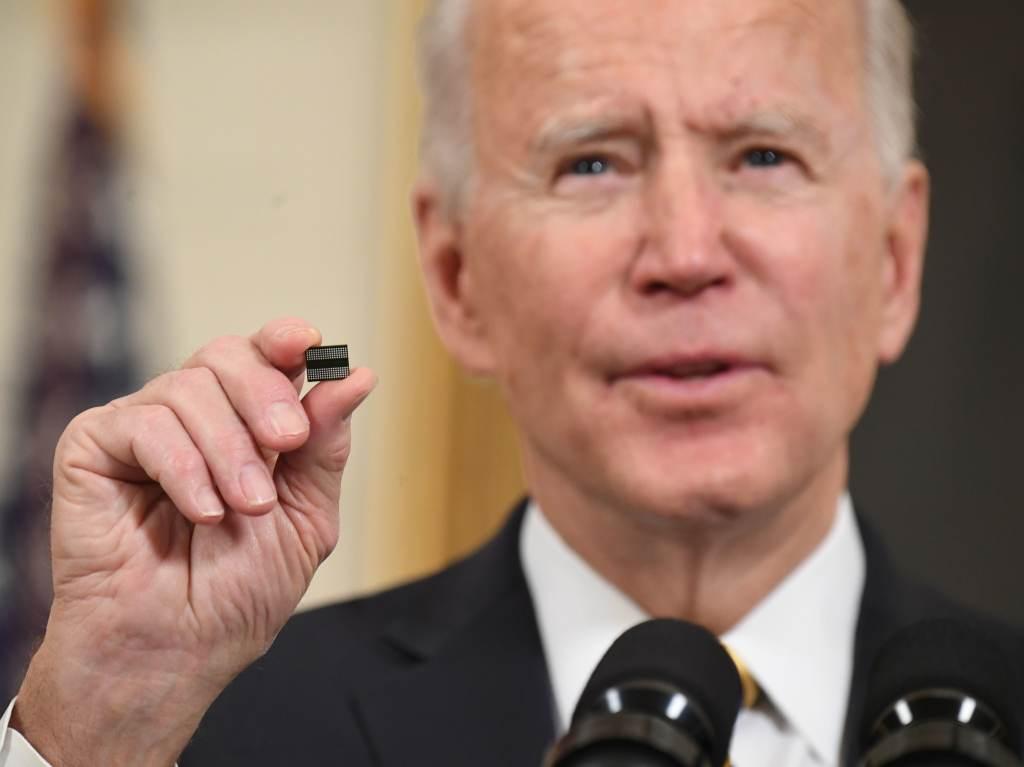 Joe Biden holds a microchip as he speaks
