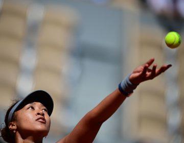 Japan's Naomi Osaka eyes the ball as she serves to Romania's Patricia Maria Tig