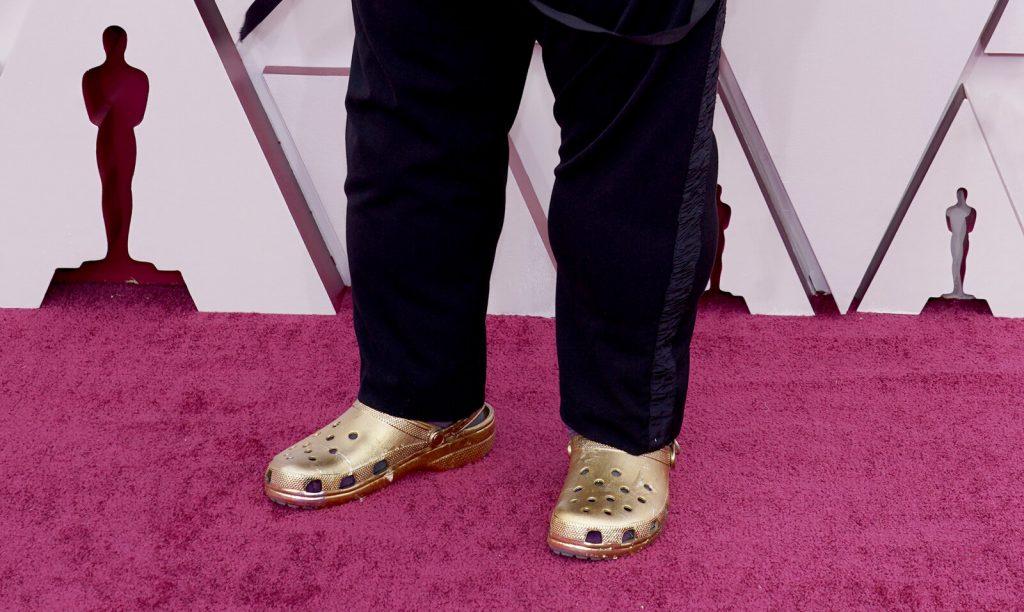 A closeup of gold Crocs worn by Questlove on a pink carpet