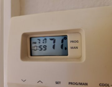 Close-up of a wall-mounted digital thermostat, reading 71 degrees Fahrenheit