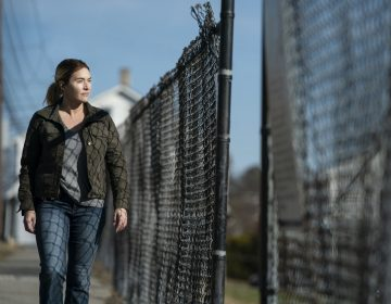 Kate Winslet, portraying her character Mare, walks along a fence