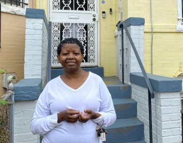 Katherine Gaines stands in front of her childhood home in Washington, D.C. She moved back in two years ago to help care for her mother, who has Alzheimer's disease. (Andrea Hsu/NPR)