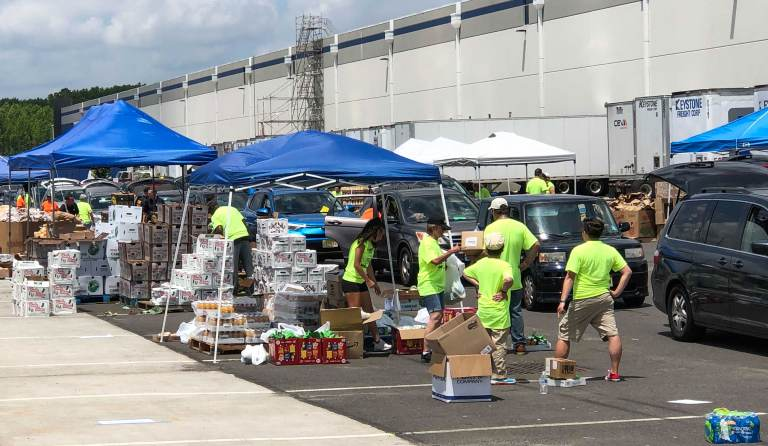 Volunteers load groceries into vehicles during a food distribution event
