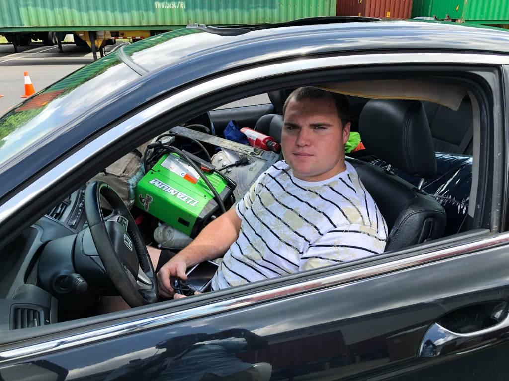 William Raymond sits inside his car