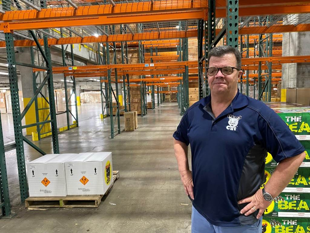 Mike Collar stands inside a warehouse