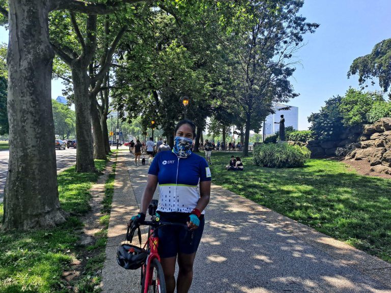 Jessica Perry stands with her bike while wearing a face mask
