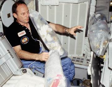Astronaut Jack R. Lousma, STS-3 commander, wearing communication kit assembly mini headset, gathers three freefloating plastic trash bags filled with empty containers, paper towels, straws, etc. Lousma will stow them in a designated stowage volume. (NASA)